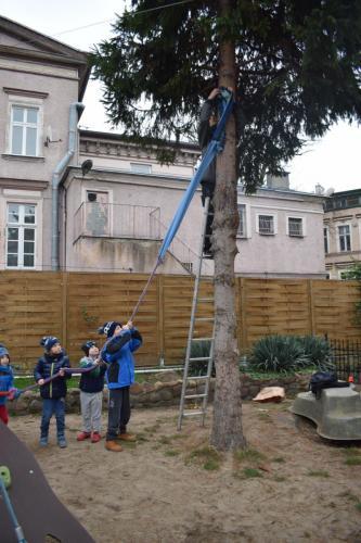 Zawieszanie futerka dla drzewa wykonanego zpołączonych szalików - plenerowa Przestrzeń sensoryczna