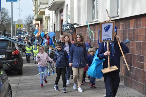 Marsz ulicami miasta zartystycznymi  transparentami wykonanymi przezdzieci - manifestacja kultury autyzmu